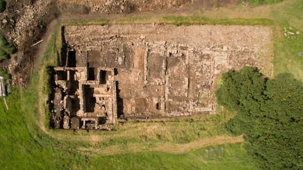 The vicus trench from above. To the right, three strip-buildings are visible, while the bathhouse occupies the bottom left of the trench. The remainder of the bathhouse remains buried beyond the trench edge to the left. (Photo: Aerial-Cam, www.aerial-cam.co.uk)