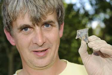 Jim Rylatt, a Post Graduate student from the University of Manchester with a Neolithic chisel arrowhead/Aerial-Cam